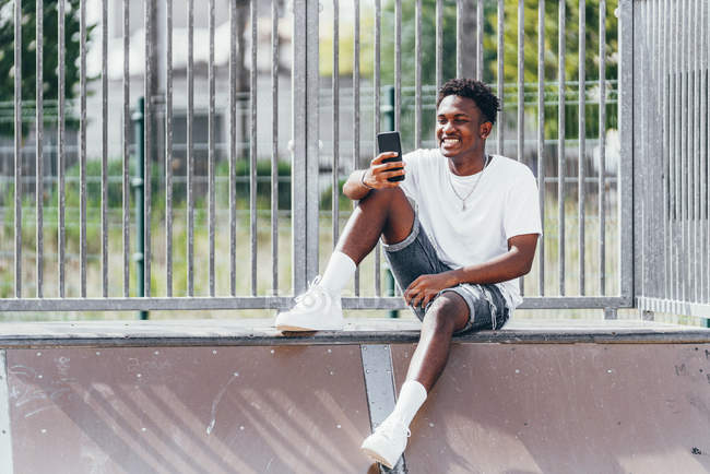 Pensive African American sportsman surfing mobile phone on playground fence in bright day — Stock Photo