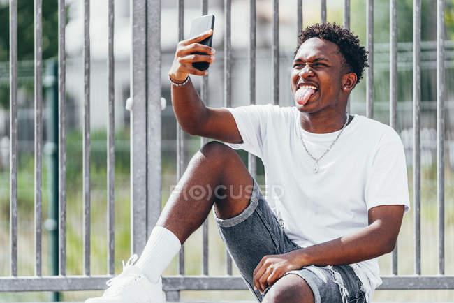 Pensivo esportista afro-americano surfando celular na cerca do playground em dia brilhante — Fotografia de Stock