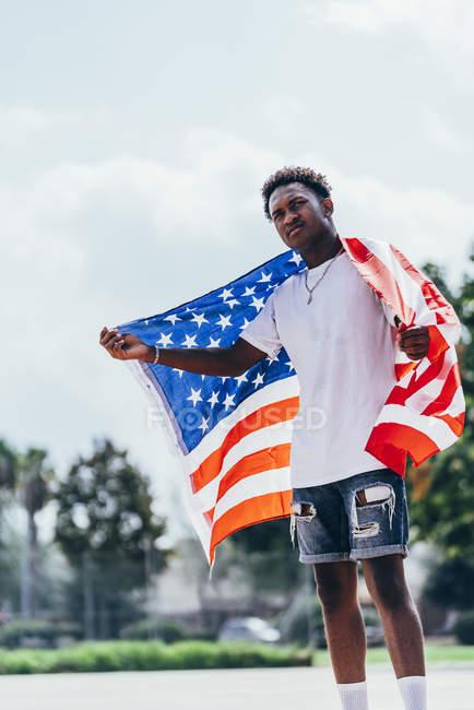 Серьезный афроамериканец, держащий американский флаг на плече и отворачивающийся — стоковое фото