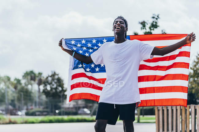 Serious African American man holding American flag on shoulder and looking away — Stock Photo