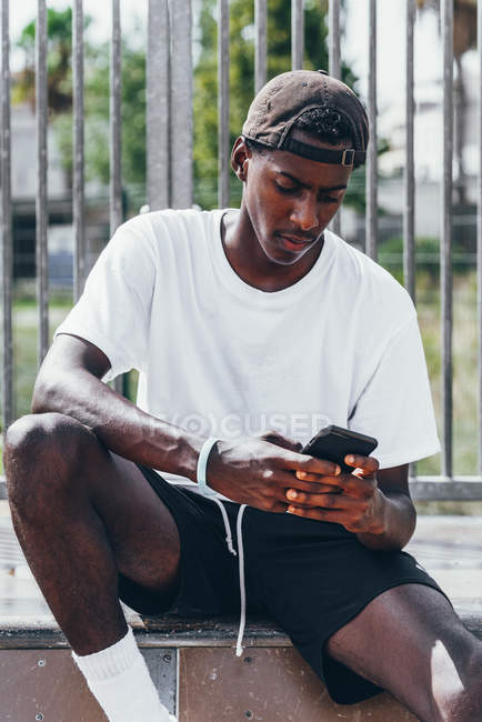 Pensativo deportista afroamericano surfeando teléfono móvil en la cerca del patio de recreo en día brillante - foto de stock