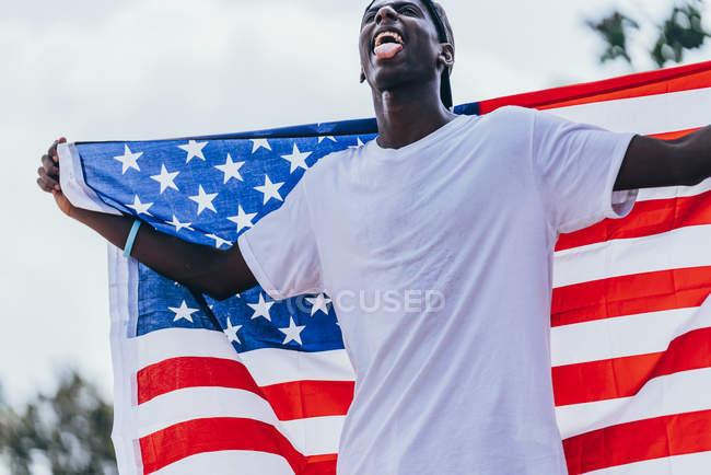 Grave uomo afroamericano che tiene la bandiera americana sulla spalla e distoglie lo sguardo — Foto stock