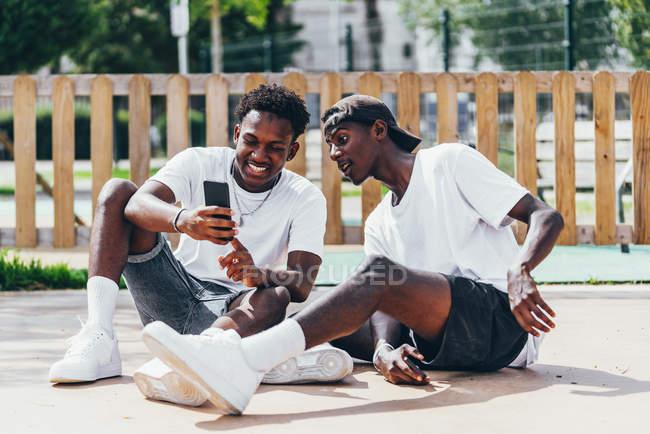 Alegre divertidos deportistas afroamericanos surfeando teléfono móvil cómodo colocado en el patio de recreo en día brillante - foto de stock