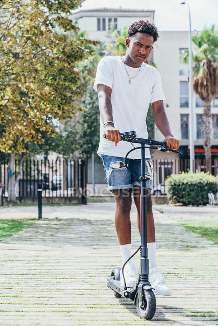 From below African American sportive man riding on electric scooter in bright cloudy day — Stock Photo