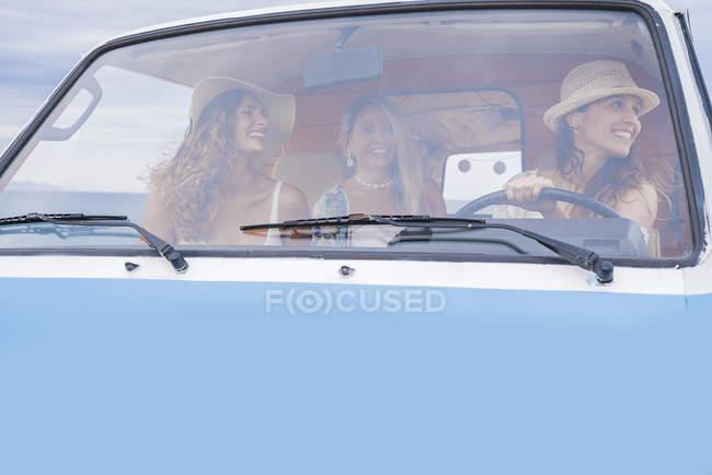 Група туристичних чарівних жінок у капелюхах у поїздці на блакитному фургоні. — стокове фото