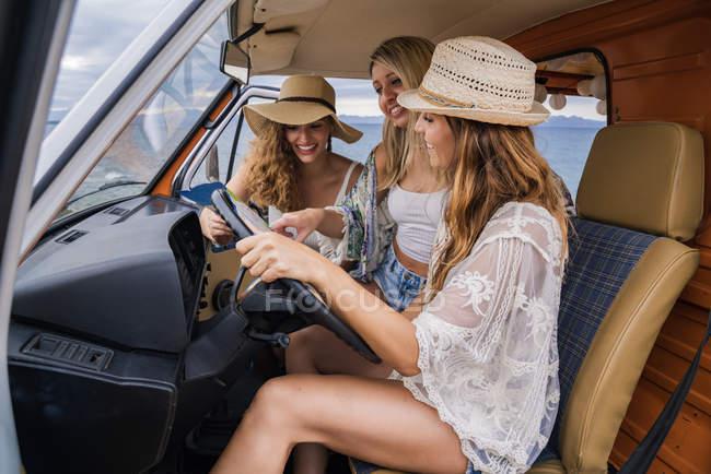Jovens mulheres olhando para o mapa dentro minivan — Fotografia de Stock
