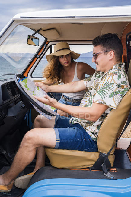 Active smiling man in sunglasses looking at open road map and finding route with woman in hat in car — Stock Photo