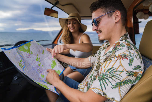 Side view of active smiling man in sunglasses looking at open road map and finding route with woman in hat in car — Stock Photo