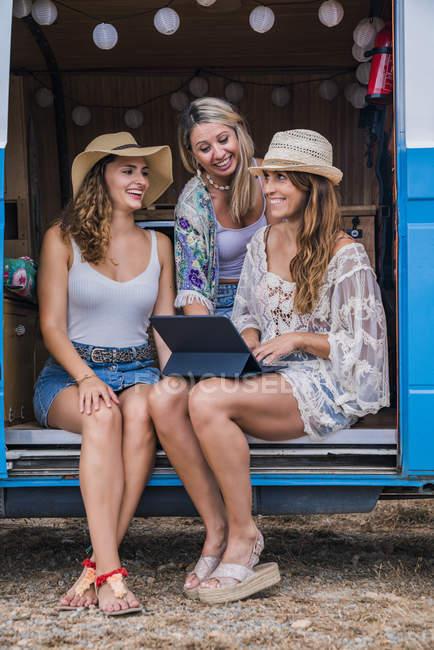 Affascinanti donne dai capelli lunghi in estate indossano navigando tablet digitale e parlando con il sorriso seduto nel salone di auto — Foto stock