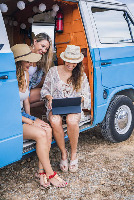 Charming long-haired women in summer wear browsing tablet and talking with smile sitting in car salon — Stock Photo