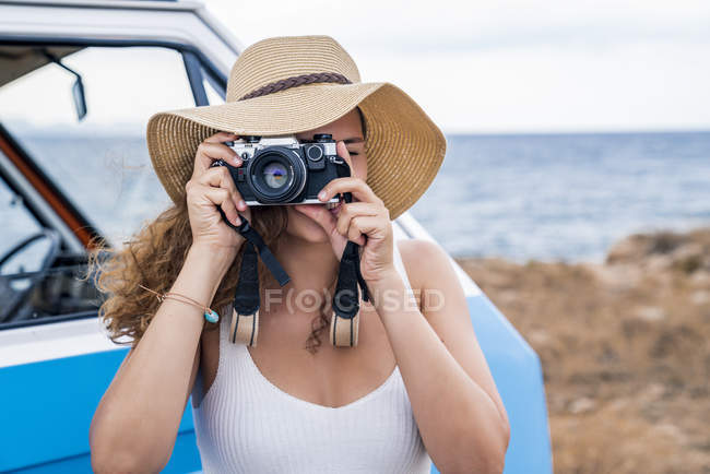 Active enthusiastic lady in hat photographing on camera in hands nearby blue car on beach — Stock Photo