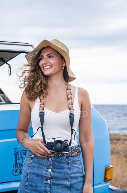 Обаятельная веселая дама в шляпе держит камеру рядом синий автомобиль на пляже и оглядывается вокруг — стоковое фото