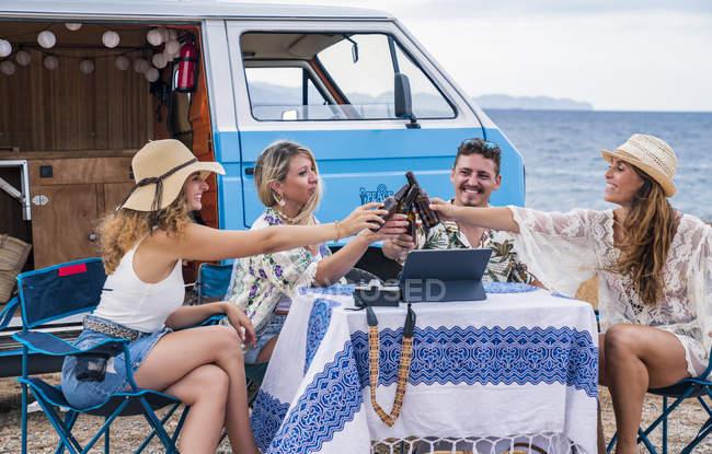 Усміхнені друзі збирають пляшки з напоїв і чіпляються за відпочинок за столиком для пікніків біля фургона. — стокове фото