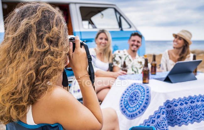 Cheerful friends smiling and holding bottles of drinks sitting at table while long-haired woman taking photo nearby blue car — Stock Photo