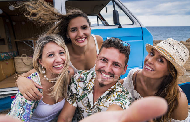 Laughing group of young people having fun taking selfie by blue minivan on beach in sunny daytime — Stock Photo