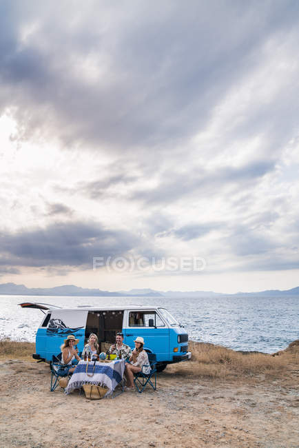 Group of friends sitting in chairs by picnic table next to blue minivan — стокове фото