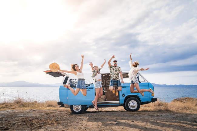 Веселые туристы прыгают с поднятыми руками на ярком минивэне на пляже в солнечный день — стоковое фото