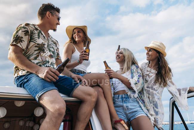Señoras perezosas alegres con el pelo largo en sombreros levantando botellas de bebidas y tintineo con el hombre con estilo en el techo del coche - foto de stock