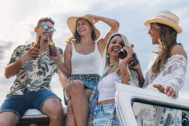 Cheerful lazy ladies with long hair in hats raising bottles of drinks and clinking with stylish man in car roof — Stock Photo