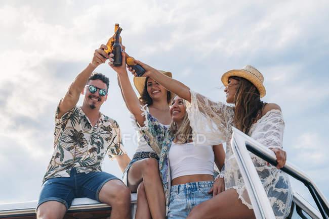 Веселые ленивые дамы с длинными волосами в шляпах, поднимающие бутылки с напитками и звенящие со стильным мужчиной на крыше автомобиля — стоковое фото