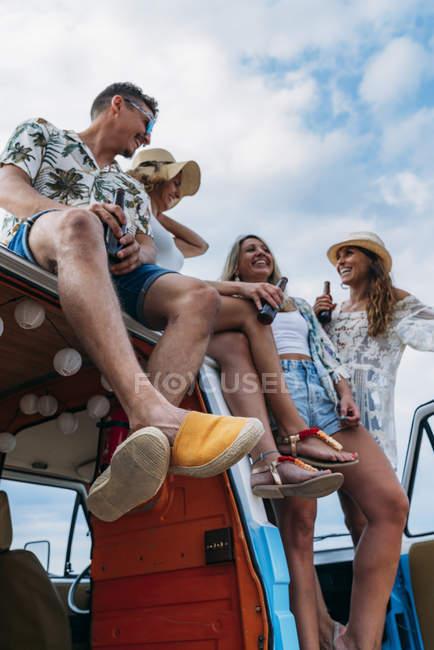 Весела група молодих чоловіків і жінок з пляшками, що сидять на даху яскравого мінівену на пляжі в сонячний день. — стокове фото