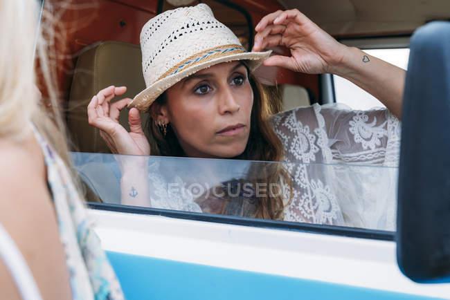 Piacevole signora affascinante in cappello distogliendo lo sguardo con il sorriso mentre si apre la porta della macchina sulla spiaggia — Foto stock