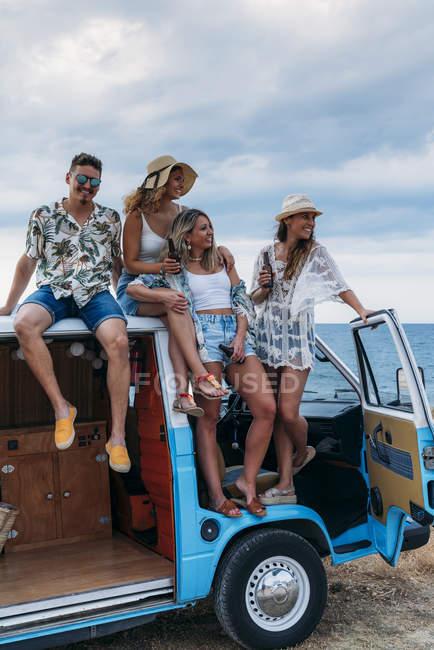 Весела група молодих людей з пляшками сидять на даху яскравого мінівену на пляжі в сонячний день. — стокове фото