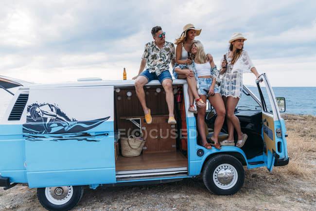 Веселая компания молодых людей с бутылками, сидящих на крыше яркого минивэна на пляже в солнечный день — стоковое фото