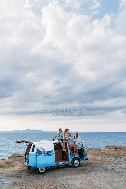 Cheerful group of young people with bottles bonding sitting on roof of bright minivan on beach in sunny daytime — Stock Photo