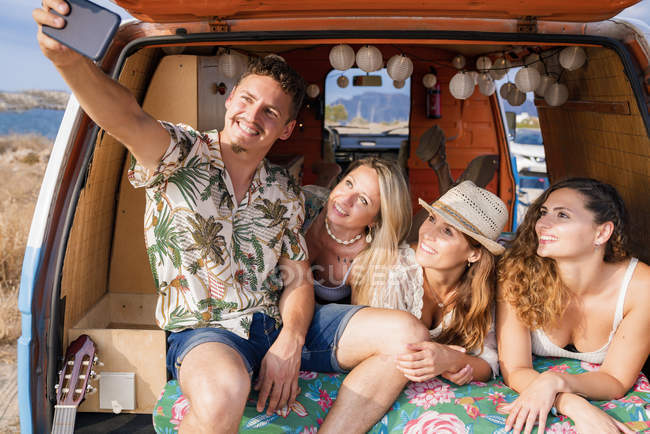 Pleasant group of young friends in trunk of minivan taking selfie on phone on beach in sunny daytime — Stock Photo