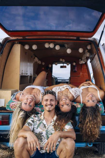 Piacevoli signore e uomini sdraiati nel bagagliaio di teste appese minivan e guardando in camera sulla spiaggia — Foto stock