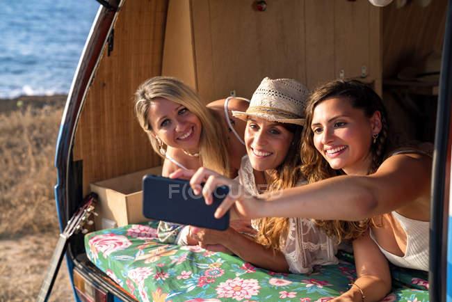 Веселые приятные дамы в багажнике яркого минивэна веселятся, делая селфи на мобильном телефоне на пляже в солнечный день — стоковое фото