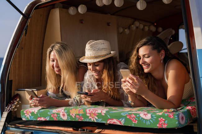 Dames agréables souriantes allongées sur le tronc de minifourgonnette lumineuse et surfant sur les téléphones mobiles sur la plage pendant la journée ensoleillée — Photo de stock