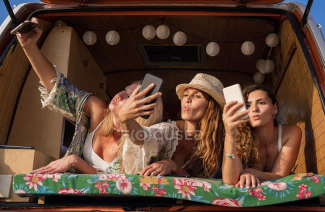 Le signore piacevoli allegre che si trovano su tronco di minivan lucente e si divertono prendendo selfie su telefoni cellulari su spiaggia — Foto stock