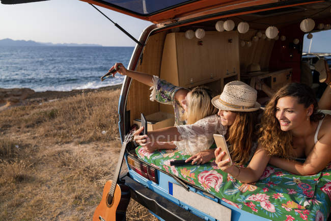 Cheerful pleasant ladies lying on trunk of bright minivan and having fun taking selfies on mobile phones on beach — Stock Photo