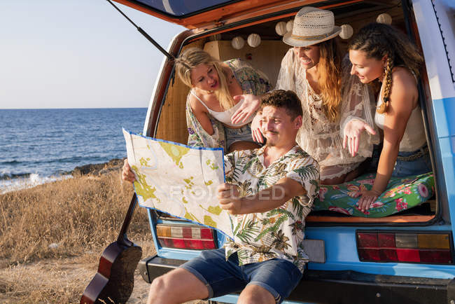 Active curios man looking at open road map and finding route with charming women in hats in open trunk of car on seaside — Stock Photo
