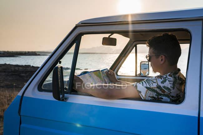 Seitenansicht eines aufmerksamen Mannes im Tropenhemd, der sich auf die Karte konzentriert, während er in einem geparkten blauen Van sitzt — Stockfoto