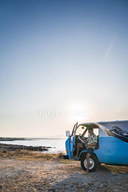 Homem atencioso em camisa tropical com foco no mapa enquanto se senta em van azul estacionado com porta aberta na praia — Fotografia de Stock
