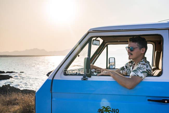 Seitenansicht eines Mannes mit Sonnenbrille und lässiger Kleidung, der nachdenklich wegschaut, während er allein in einem geparkten blauen Lieferwagen sitzt — Stockfoto