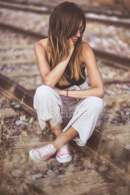 Mujer de pelo largo sentada en ferrocarriles cubiertos de hierba seca - foto de stock