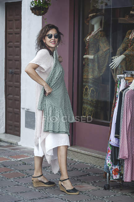 Side view of successful confident smiling cheerful woman choosing polka-dot dress during shopping on street — Stock Photo
