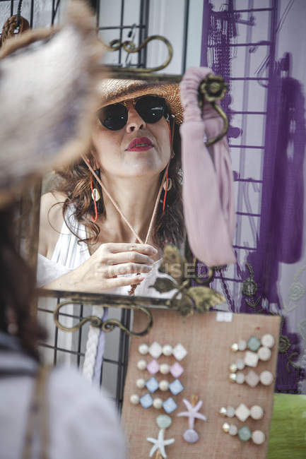 Stylish confident woman in sunglasses looking in reflection of mirror for checking straw hat with cord at town market — Stock Photo