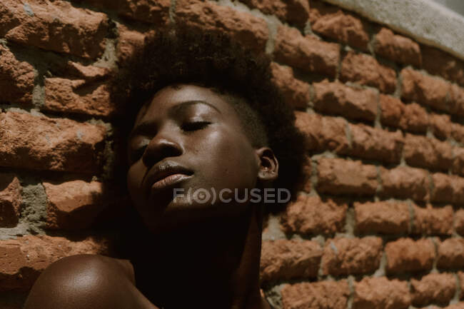 Young black woman with eyes closed against wall — Stock Photo