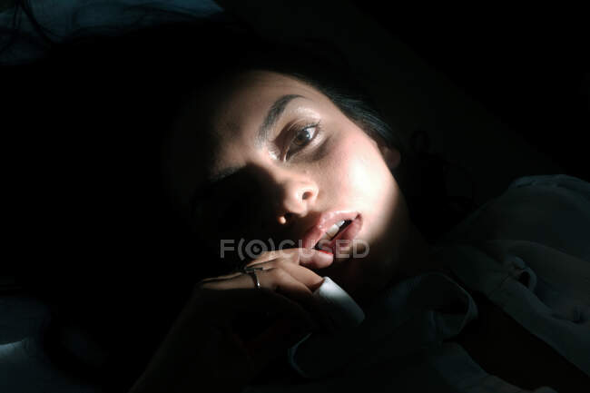 Gorgeous sensual woman lying in darkness — Stock Photo