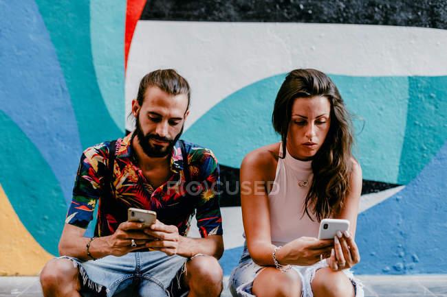 Casal sentado no chão e navegando smartphones — Fotografia de Stock