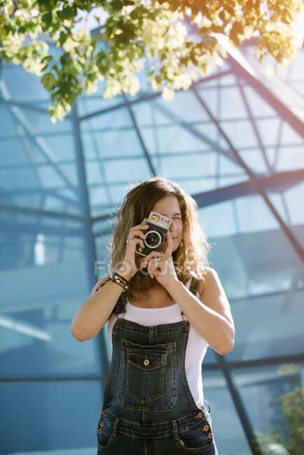 Giovane donna entusiasta cattura momento scattare foto sulla macchina fotografica su sfondo di architettura di vetro — Foto stock
