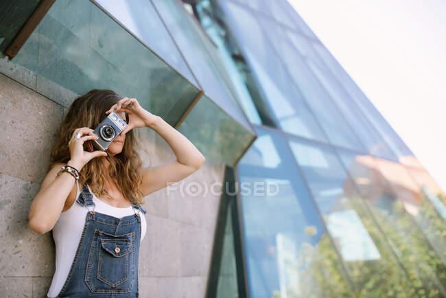 Jovem mulher entusiasta captura momento tirar foto na câmera no fundo da arquitetura de vidro — Fotografia de Stock