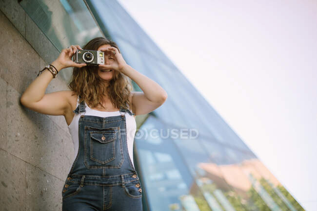 Young enthusiastic woman capturing moment taking picture on camera on background of glass architecture — Stock Photo