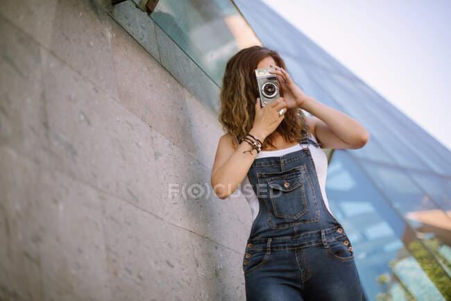 Молодая увлеченная женщина снимает момент на камеру на фоне стеклянной архитектуры — стоковое фото