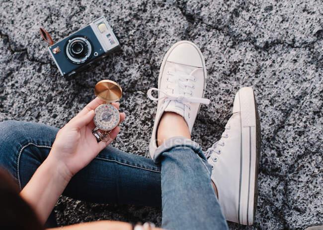 D'en haut boussole ouverte dans les mains de la femme créatrice de culture avec appareil photo naviguant pour déterminer la direction — Photo de stock